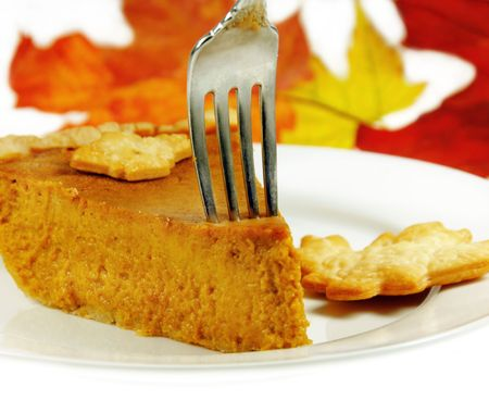 Pumpkin Pie with a fork and fall leaves in the background. photo