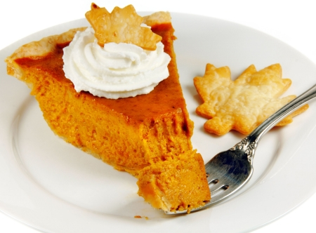 Pumpkin pie with whipped cream on a white plate with a fork. photo