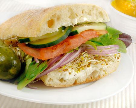 Healthy vegetarian sandwich with cucumbers, tomatoes, lettuce, onions and sprouts. photo