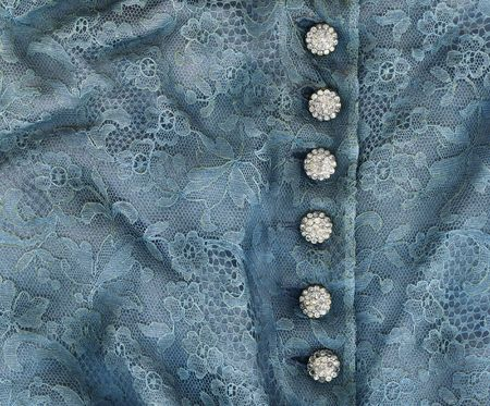 expensive: Dress detail of blue lace with diamond buttons for use as a background texture.