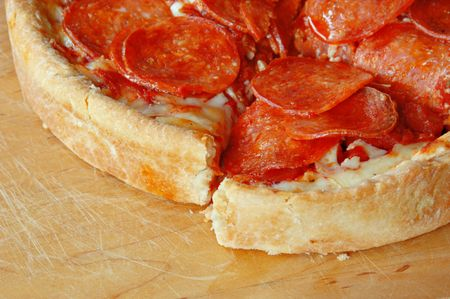 Sliced deep dish pepperoni pizza.  photo