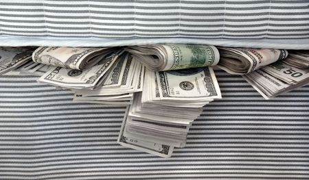 onehundred: Cash stashed for safe keeping in between mattresses. Stock Photo