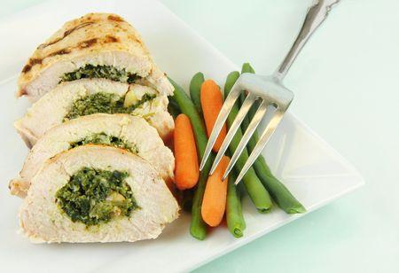 하얀 접시에 야채와 함께 구운 하 고 얇게 썬 닭고기 피렌체.