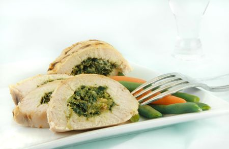florentine: Grilled and sliced chicken florentine with vegetables on a white plate.