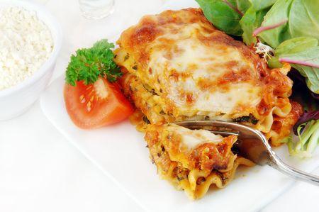 Lasagne met spinazie salade op een witte plaat.