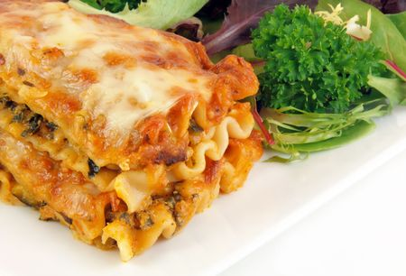 Close up image of spinach lasagna with salad on a white plate.
