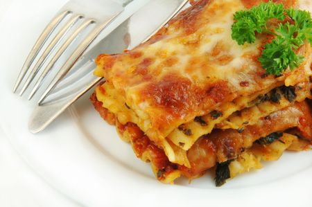 Serving of spinach lasagna close up with a knife and fork on a white plate. Stock Photo