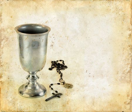 rosary: Chalice for communion and a rosary on a grunge background.