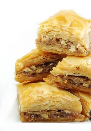 stacked up: Baklava stacked up high on a white background.