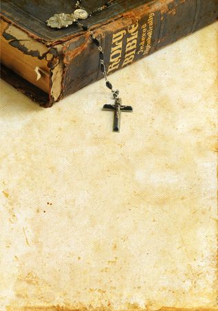 Antique Bible with rosary beads on a grunge background with plenty of copy-space for your text.
