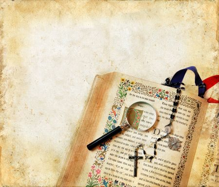 Open Catholic Bible, rosary beads and a magnifying glass on a grunge background.
