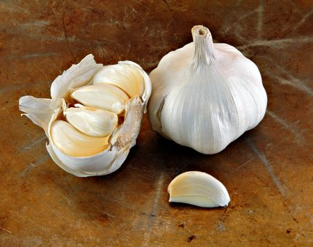 Whole garlic and cloves on a rustic surface. Archivio Fotografico