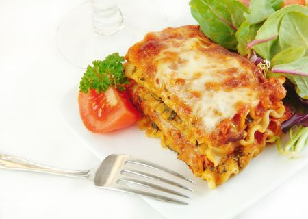 lasagna: Lasagna and salad on a white plate with a fork.