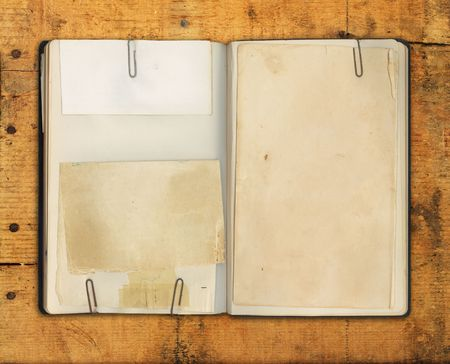 Old blank book on weathered wood with rusty nails and cracks for background texture. Stock Photo