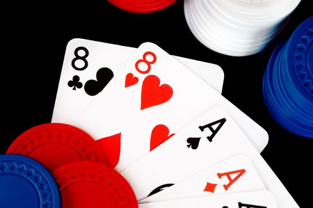 eights: Winning poker hand with chips on a black background.