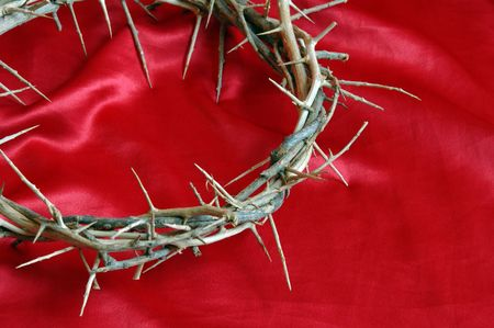 Crown of Thorns on red satin fabric background. photo