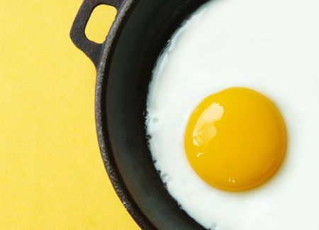 Fried egg in an iron skillet on yellow background.