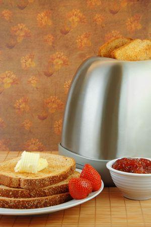 Vers gemaakte toast met jam en boter op een witte plaat.