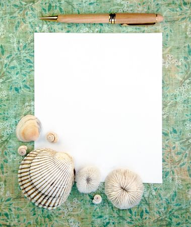 Notepaper and pen with sea shells on a green background.