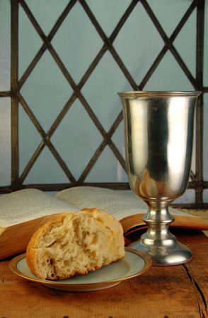 devout: Communion bread and wine with Bible on a rustic surface in front of a leaded glass window.