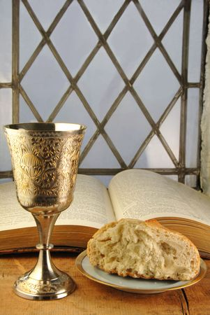 Communion bread and wine with Bible on a rustic surface in front of a leaded glass window.
