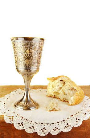 Communion bread and wine on white lace.