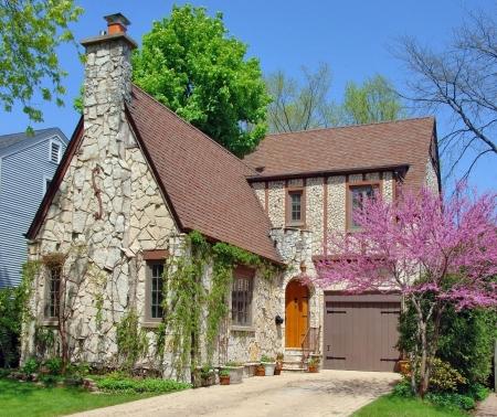 tudor: Stone house in a peaceful suburban neighborhood. Springtime.