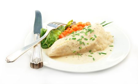 Chicken in a cream sauce with steamed vegetables on a white background.