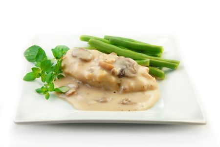 Chicken in a cream mushroom sauce with steamed vegetables on a white background.