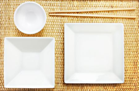Empty White dishes and wooden chopsticks on a bamboo mat.