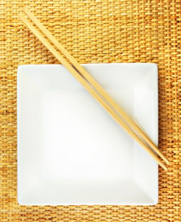 Empty White dishe and wooden chopsticks on a bamboo mat. photo