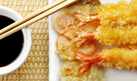 soysauce: Shrimp Tempura with with vegetables and chopsticks on a white plate.