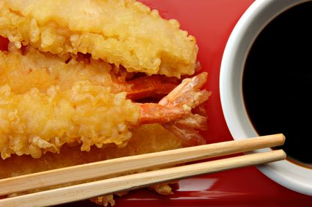 Shrimp Tempura and soy sauce with chopsticks on a red plate. Stock Photo
