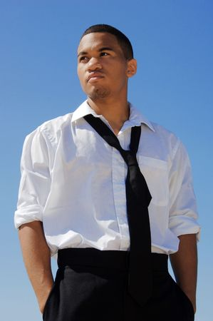 Young man in a white shirt and black tie against the blue sky. photo