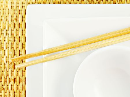 White dishes and wooden chopsticks on a bamboo mat. photo