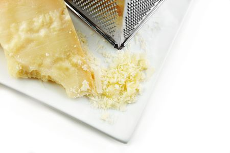 Parmesan cheese freshly grated onto a square white plate.