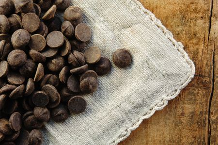 Dark chocolate chips spilled out onto a rustic table.