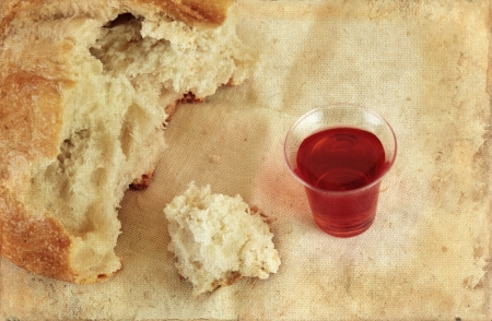 offering: Communion bread loaf and wine on a grunge background.