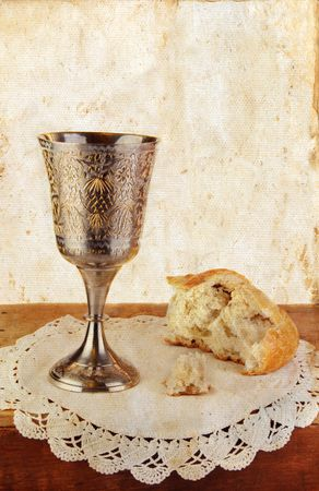 Communion bread and wine on white lace. photo