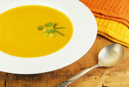 Squash soup  in white bowl with a spoon on a rustic wood table. photo