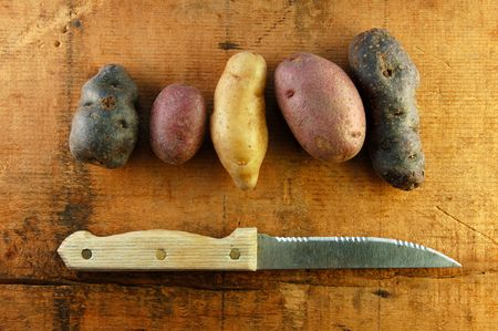 fingerling: Variety of fingerling potatoes with a knife on a wooden surface. Stock Photo