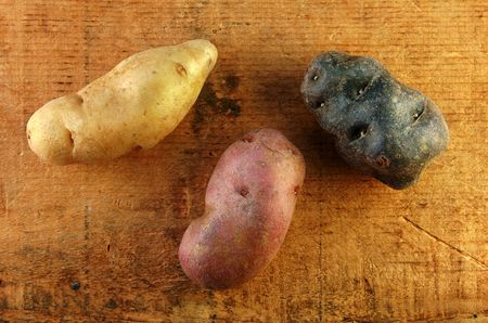 fingerling: Three different colors of fingerling potatoes on a wooden table. Stock Photo
