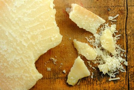 Parmesan cheese in chunks and freshly grated on a rustic wood surface. Imagens
