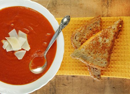 Grilled cheese sandwich and bowl of homemade tomato soup on a rustic wooden table. photo