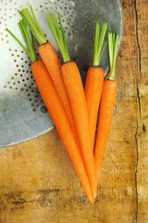 Fresh carrots in a colander on a rustic wooden table.