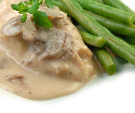 Chicken breast in mushroom sauce with green beans close up.