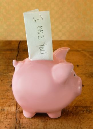 Piggy bank with an IOU note sticking out the top. Banco de Imagens