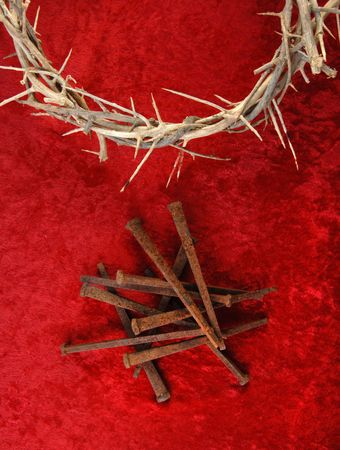 Crown of Thorns and rusty metal spikes on a rich red background. Stock Photo
