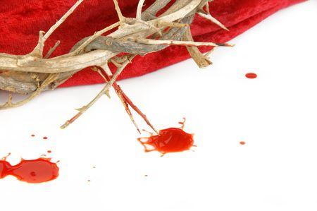 doornenkroon: Kroon van doornen op rode stof en druppels bloed op wit.