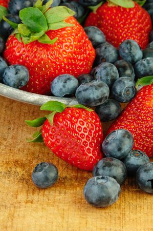 a colander: Fresh strawberries and blueberries in a colander on rustic wooden table. Stock Photo